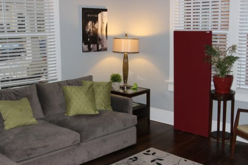GIK Acoustics Freestand Acoustic Panel red next to couch